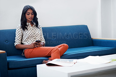 Buy stock photo Shot of a businesswoman using her cellphone while sitting on a sofa in the office