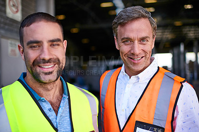 Buy stock photo Portrait of two smiling workers standing in a large warehouse