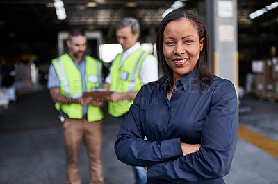 Buy stock photo Portrait of a warehouse manager standing arms folded with workers in the background