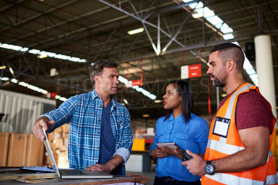 Buy stock photo Shot of a group of coworkers talking together over a laptop while standing in a large warehouse