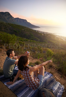 Buy stock photo Shot of a young couple taking pictures on a phone during their date outdoors
