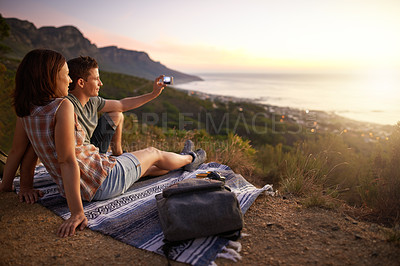 Buy stock photo Shot of a young couple taking a selfie on their date outdoors