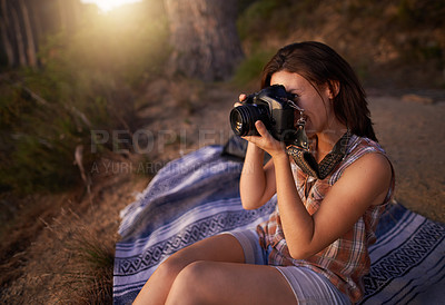 Buy stock photo Shot of a young woman taking pictures with her camera outdoors