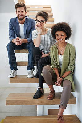 Buy stock photo Portrait of three young creatives sitting on a staircase in a modern office