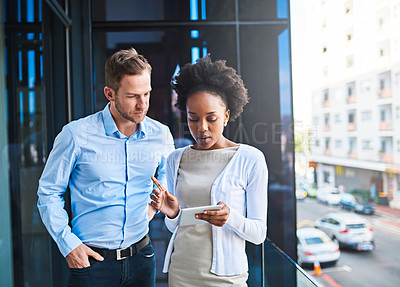 Buy stock photo Cropped shot of two coworkers using a digital tablet while standing on a balcony