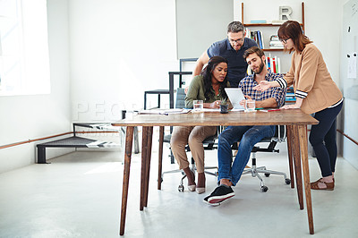 Buy stock photo Shot of a group of creative businesspeople working together on something on a tablet