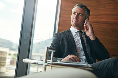 Buy stock photo Cropped shot of a businessman answering a phonecall while sitting in his office