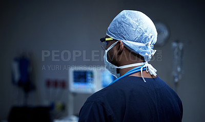 Buy stock photo Rearview shot of a surgeon standing in an operating room