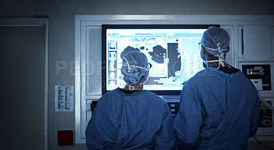Buy stock photo Shot of two surgeons analyzing a patient's medical scans during surgery