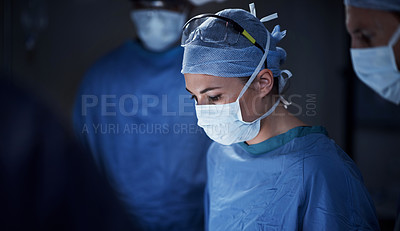Buy stock photo Cropped shot of a surgeon in an operating room with her team behind her