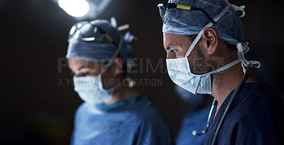 Buy stock photo Shot of a surgeon in an operating room with his assistant in the background