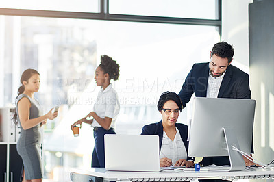 Buy stock photo Cropped shot of two businesspeople working in her office with colleagues in the background