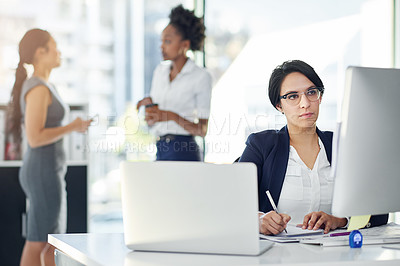 Buy stock photo Cropped shot of a businesswoman working in her office with colleagues in the background