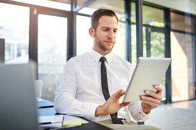 Buy stock photo Cropped shot of a businessman working on a digital tablet in a modern office