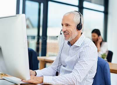 Buy stock photo Cropped shot of a mature businessman working in his office with colleagues in the background