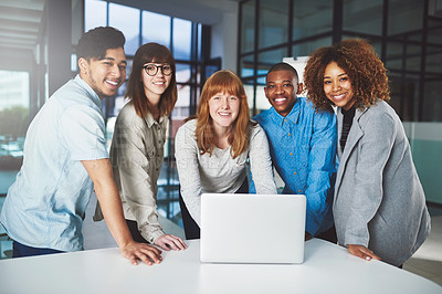 Buy stock photo Cropped portrait of a group of young businesspeople huddled around a laptop in their office