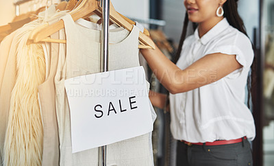 Buy stock photo Cropped shot of an unidentifiable woman rearranging clothes on a rail with a sign that reads