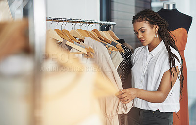 Buy stock photo Cropped shot of a young woman looking at dresses on a rail in a store