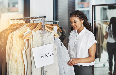 Buy stock photo Cropped shot of a woman looking at dresses on a rail with a sign that reads