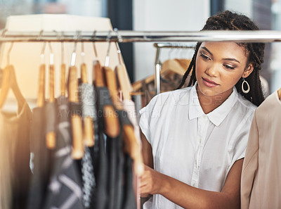 Buy stock photo Cropped shot of a woman looking at clothes on a rail in a store