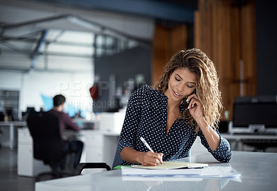 Buy stock photo Cropped shot of a young businesswoman making notes while talking on a cellphone in a modern office