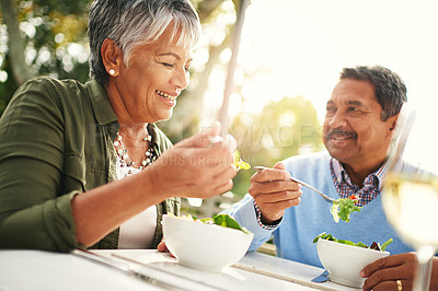 Buy stock photo Shot of a happy older couple enjoying a healthy lunch together outdoors