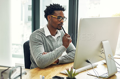 Buy stock photo Cropped shot of a young businessman working on a computer in a modern office
