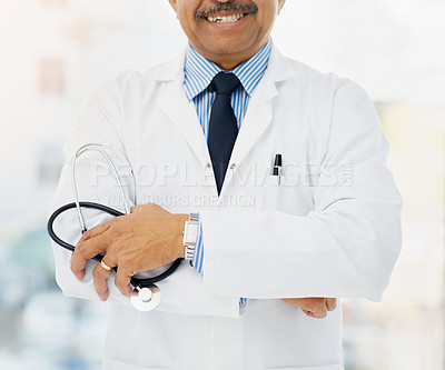 Buy stock photo Cropped shot of a doctor holding a stethoscope and folding his arms