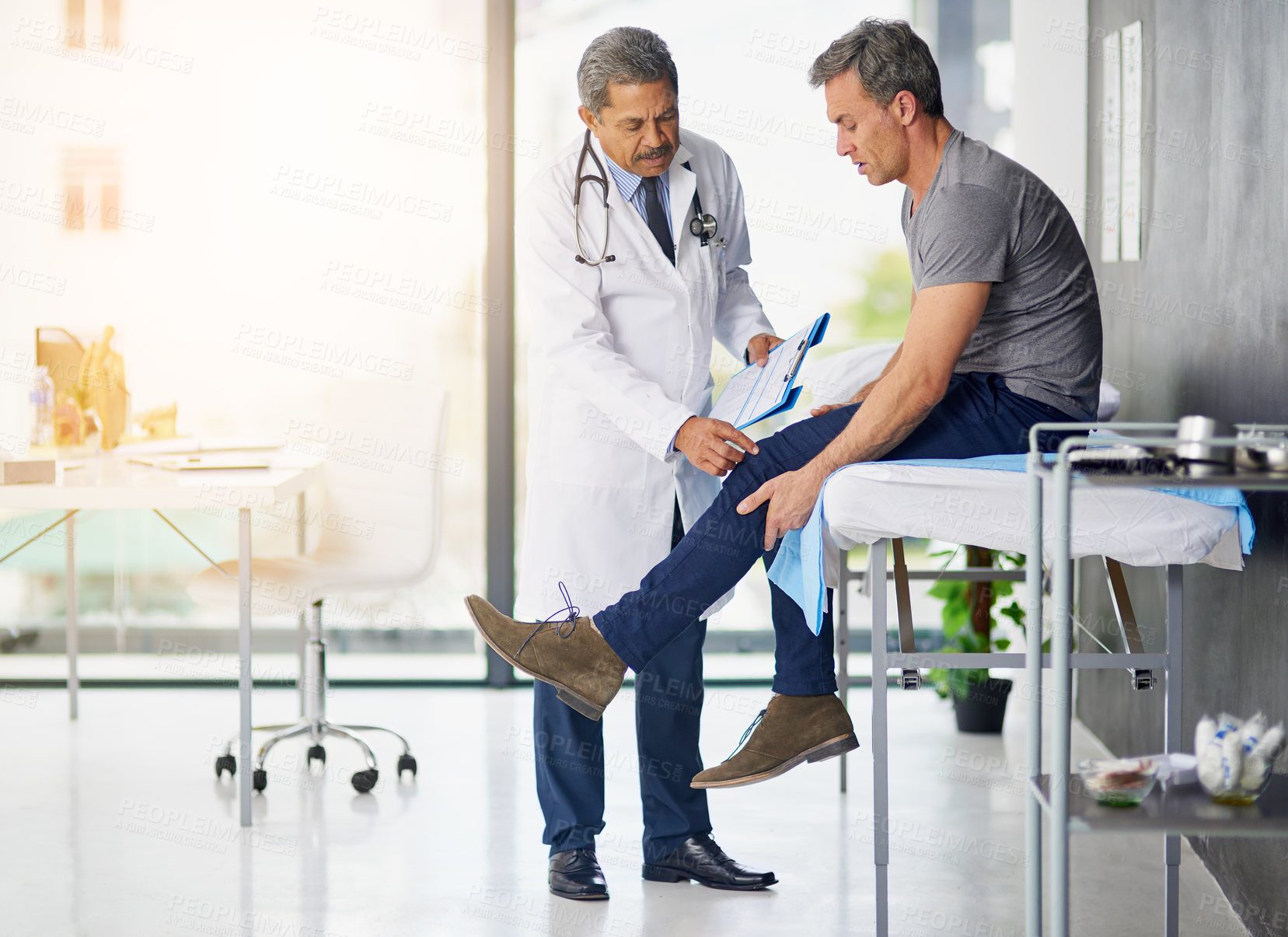 Buy stock photo Shot of a mature doctor examining his patient who is concerned about his knee