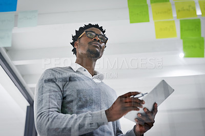 Buy stock photo Cropped shot of a young businessman writing notes on a glass wall in a modern office