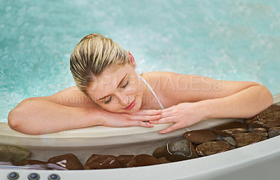Buy stock photo Shot of a young woman napping in the jacuzzi at a spa