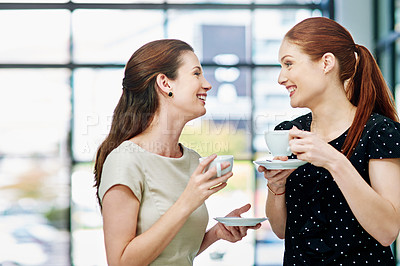 Buy stock photo Cropped shot of two businesswomen standing and chatting during a coffee break