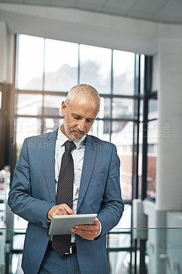Buy stock photo Cropped shot of a mature businessman working on a digital tablet in a modern office
