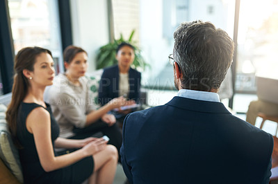 Buy stock photo Shot of a group of businesspeople listening to their manager during a meeting