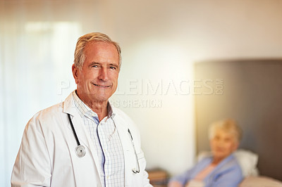 Buy stock photo Portrait of a mature doctor with his patient in bed in the background