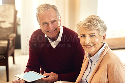Buy stock photo Portrait of a senior couple sitting in their living room while using a digital tablet