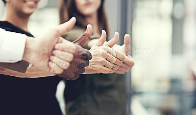 Buy stock photo Closeup shot of a group of businesspeople showing thumbs up together in an office