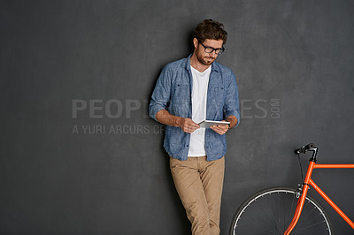 Buy stock photo Studio shot of a young man using his tablet against a grey background