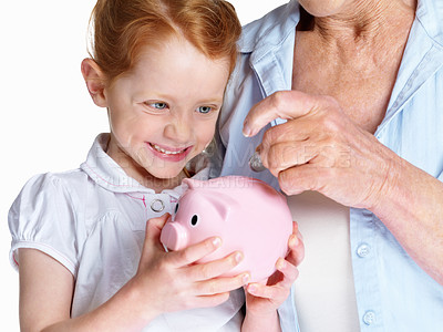 Buy stock photo Closeup of a mature woman with her granddaughter inserting a coin in piggybank