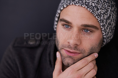 Buy stock photo Cropped shot of a stylish young man posing with his hand on his chin in the studio