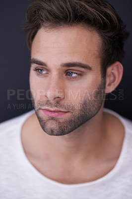 Buy stock photo Studio shot of a handsome young man posing against a dark background