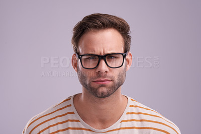Buy stock photo Studio shot of a young man looking angry against a lilac background