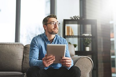 Buy stock photo Shot of a businessman using his digital tablet while sitting on a sofa in the office