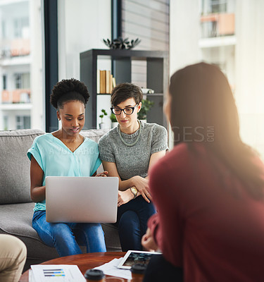 Buy stock photo Shot of colleagues working together on a laptop