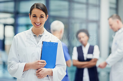 Buy stock photo Portrait of a young female doctor standing in a hospital with colleagues in the background