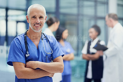 Buy stock photo Portrait of a mature male doctor standing in a hospital with colleagues in the background