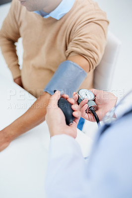 Buy stock photo High angle shot of a male doctor taking a patient's blood pressure