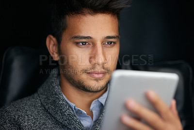 Buy stock photo Shot of a young man using a digital tablet in the dark