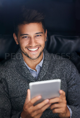 Buy stock photo Portrait of a smiling young man using a digital tablet in the dark
