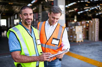 Buy stock photo Shot of two workers talking together over a clipboard inside of a warehouse